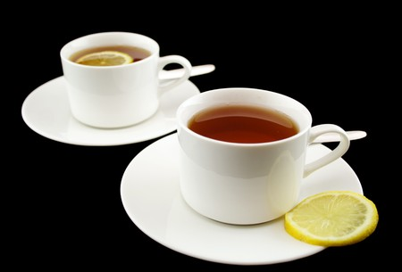 rich flavor: Two white cups of lemon tea over a black background.
