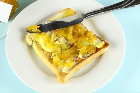 Orange marmalade spread on a slice of toast with butter. Stock Photo - 7416644