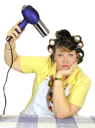 apathetic: Totally bored frumpy housewife with hair rollers dries her hair. Stock Photo