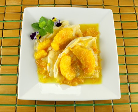 zest: Delicious orange crepes with an orange sauce with fresh zest. Stock Photo