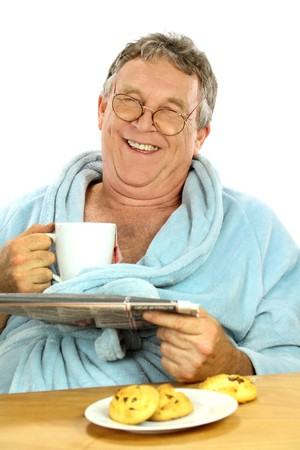 Nerdy middle aged man smiling while having breakfast and reading the paper. photo