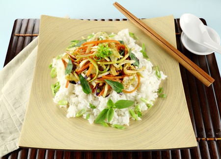 Delicious vegetarian asian stir fry on boiled white rice with thai basil and vietnamese mint. photo
