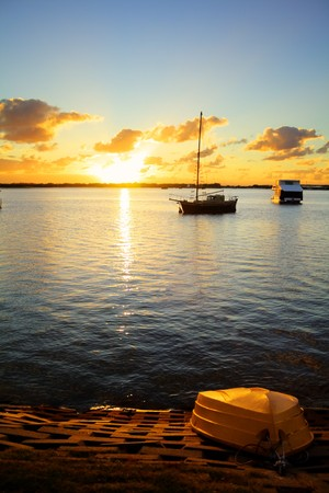 ketch: Up turned dinghy on the shore as the sun rises over the water.