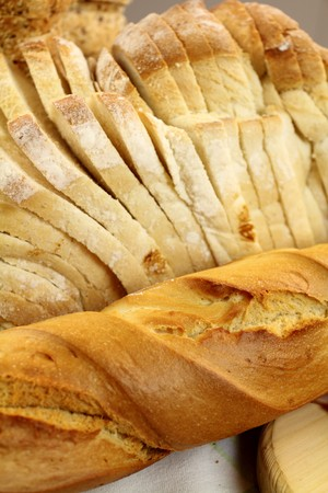 unsliced: Bread roll and sliced bread arranged as a bread background.