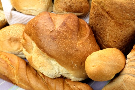 unsliced: Background of different bread textures with loaves and bread rolls.