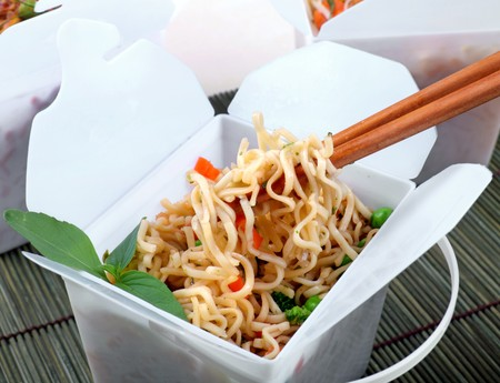 Take away egg noodles on chopsticks in a take away container. Stock Photo