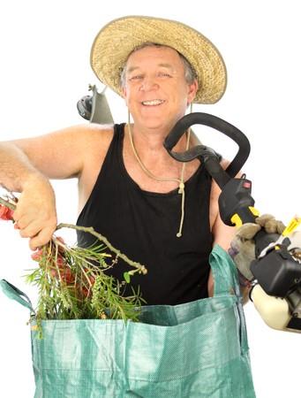 clippings: Jardinero de edad media con un cortador de c�sped pone sus recortes de jard�n en una bolsa de basura.