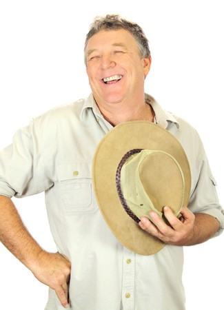 Middle aged laughing man standing and holding hat. photo