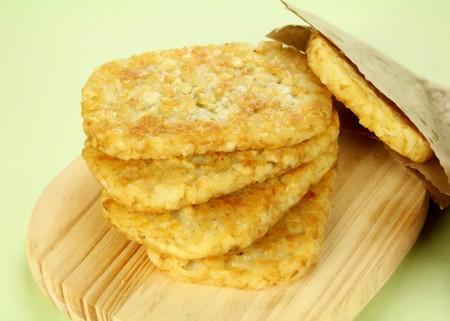 papas doradas: Pila de fritos hash browns en un tablero listo para servir.