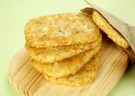browns: Stack of fried hash browns on a board ready to serve.