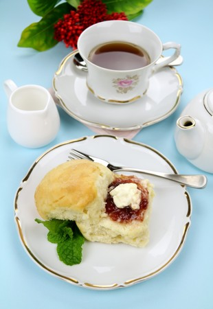 Fresh baked scones with jam and cream with a refreshing cup of tea. photo