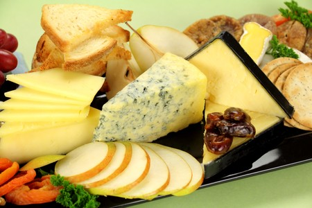 Delicious cheese platter with various cheeses and fruits ready to serve. photo