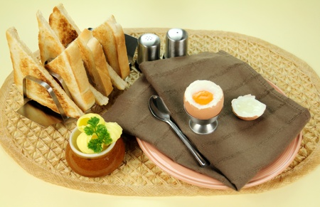 flavorful: Freshly cracked boiled egg with toast and butter for breakfast.