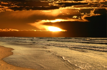Waves roll in at dawn as the sun breaks through clouds. Stock Photo