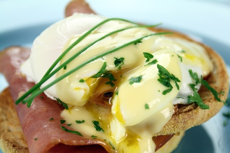 Delicious breakfast of eggs benedict with beautiful rich hollandaise sauce.