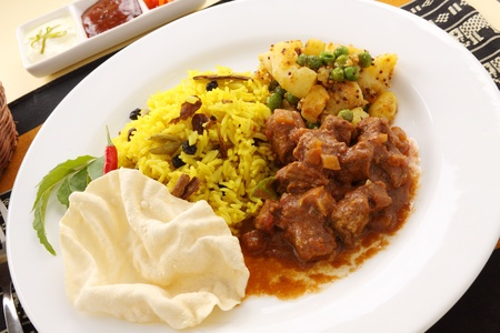 Delicious and spicy Indian beef curry served with pappadums. photo