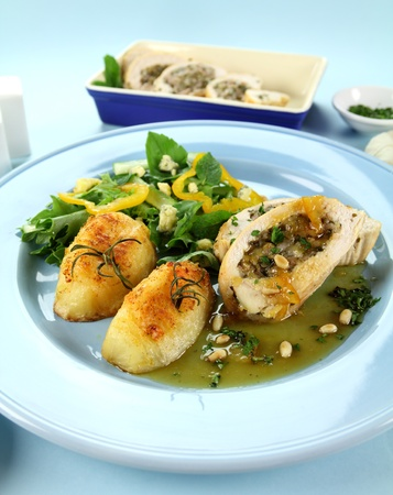 Delicious stuffed chicken and potatoes and salad with a piquant sauce. photo