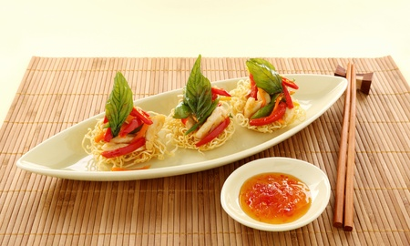 Delicious Asian chilli chicken on beds of crispy noodles. Stock Photo - 8862626