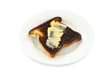 A piece of burnt toast spread with butter. photo