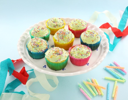 A plate of delicious iced cup cakes for a birthday celebration. photo