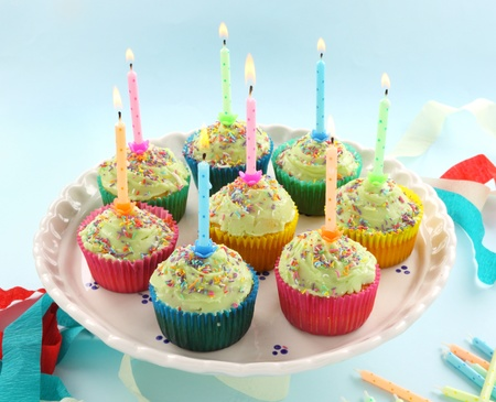 Birthday cup cakes all with their own candles burning. photo