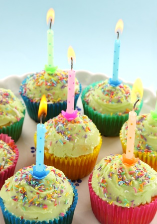 Birthday cup cakes all with their own candles burning. Stock Photo - 8953197
