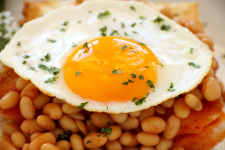 Delicious old fashioned breakfast of a fried egg on a baked beans stack on toast.