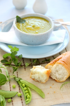 Delicious pea soup with fresh mint and crusty bread. photo