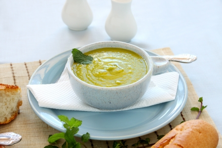 Delicious pea soup with fresh mint and crusty bread. Stock Photo