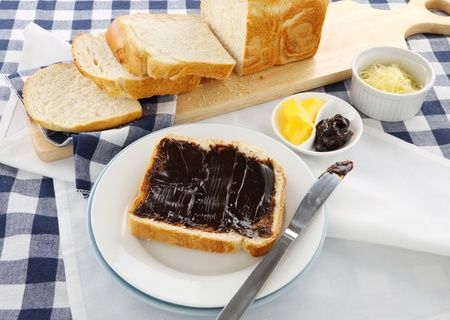 The iconic Australian spread vegemite on to a slice of fresh bread.