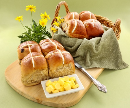 Hot cross buns in a basket and some with butter and daisies. photo
