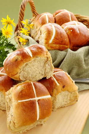 Hot cross buns in a basket with daisies ready to serve.
