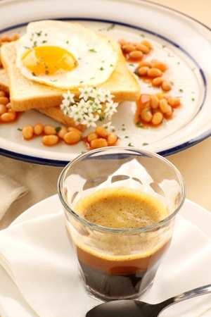 Fried egg with beans with a strong short black coffee. Stock Photo - 9369187