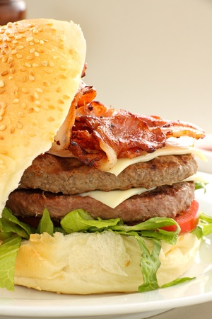 Double decker hamburger with bacon and cheese ready to serve. photo