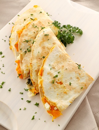 Delicious pumpkin quesadilla sliced and ready to serve with chopped parsley.