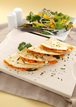 Delicious pumpkin quesadilla sliced and ready to serve with a garden salad. photo