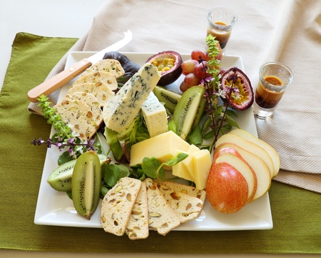 Delicious fruit and cheese platter featuring a variety of different cheeses and fresh fruits. photo