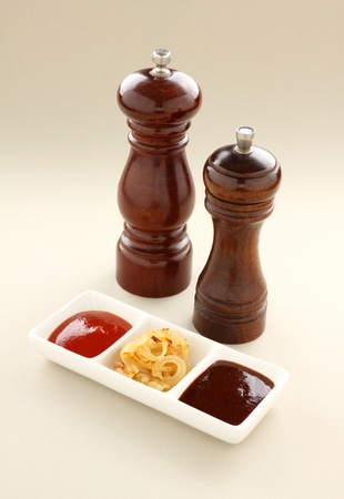 bbq sauce: Salt and pepper mills with condiments of ketchup, BBQ sauce and fried onion.