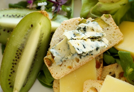 Fresh kiwi fruit with blue cheese on pistachio bread withsalad. photo