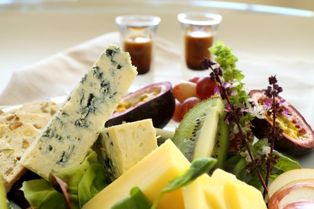 Delicious fruit and cheese platter featuring different cheeses and fresh fruits with a coffee liquer. photo