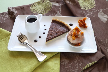 Delicious slice of chocolate tart with honeycomb and caramel ice cream. photo