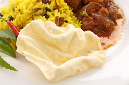 sultanas: Crispy fried pappadum with Indian beef curry. Stock Photo