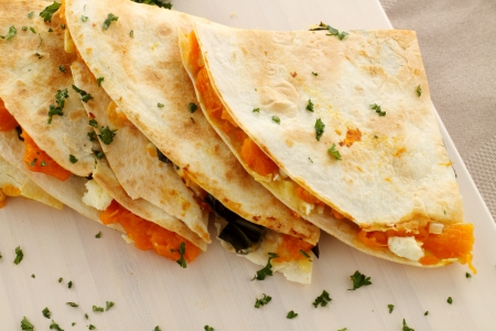 mexican food: Delicious pumpkin quesadilla sliced and ready to serve with chopped parsley.