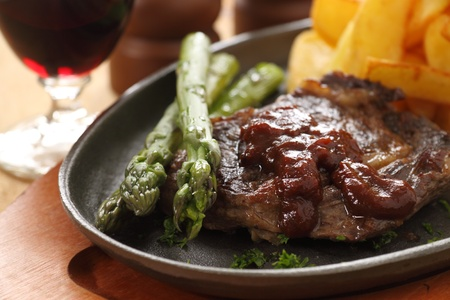 Grilled fillet steak with asparagus and barbeque sauce with potato wedges. Stock Photo
