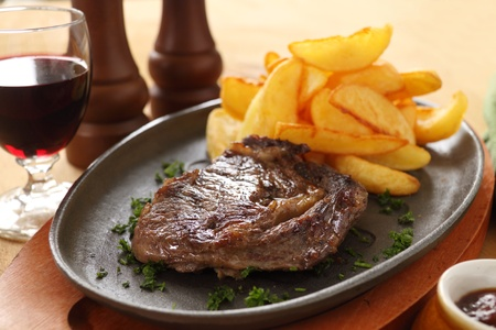 Grilled rib fillet steak with fried chips ready to serve. photo