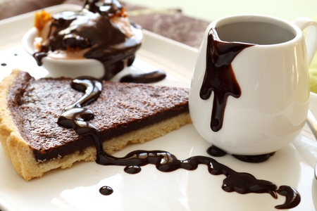 Chocolate tart slice and ice cream with melted chocolate from a jug. photo