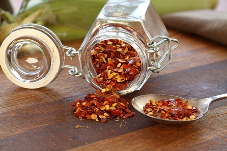 Glass container with dried chili flakes lying on a cutting board. photo
