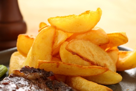 wedges: Crisp Golden potato wedges served with steak and ready to eat. Stock Photo