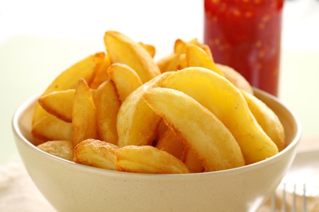 Bowl of freshly fried crisp potato wedges ready to serve. photo