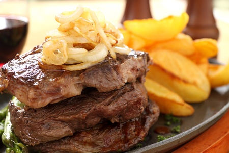 wedges: Fried onions on top of a stack of beef steaks.
